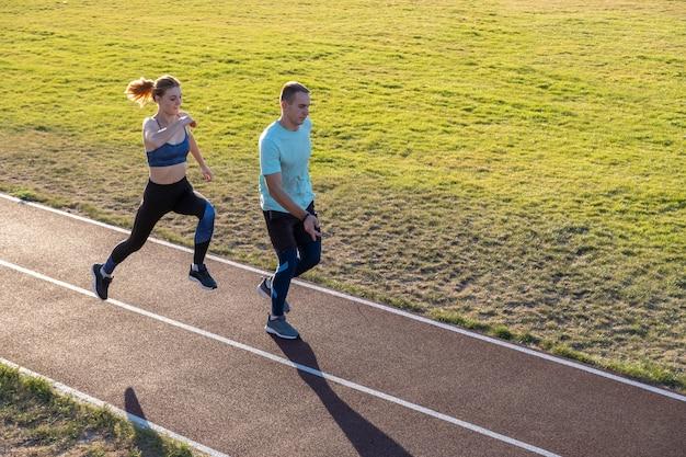 Молодые пары подходящих спортсменов мальчика и девушки бежать пока делающ тренировку на красных следах общественного стадиона outdoors.