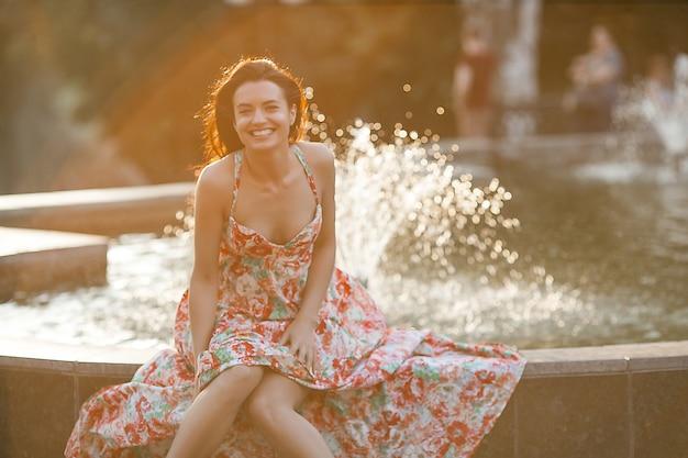 Портрет красоты женщины outdoors. привлекательная стильная молодая женщина возле фонтана в летнее время. крупным планом портрет жизнерадостная девушка.