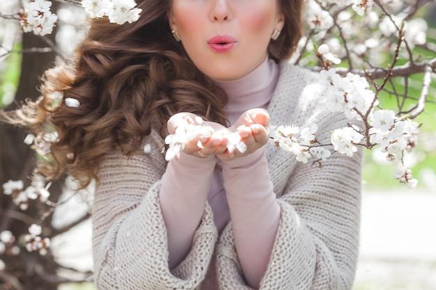 Молодая женщина с весенний подарок или подарок. красивая дама на предпосылке природного источника outdoors в саде.