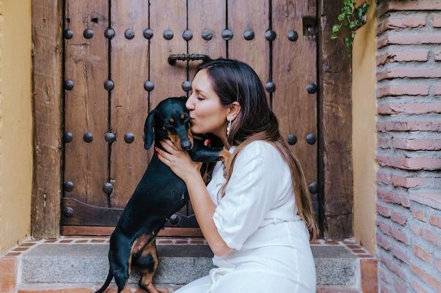 Милая маленькая собака сосиски сидя outdoors с ее предпринимателем дома. женщина целует ее собаку. концепция любви к животным