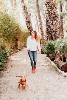 Молодая женщина гуляя с ее милым щенком кокер спаниеля outdoors