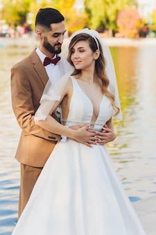 Стильный счастливый жених и невеста представляя на большом слове влюбленности в свете вечера на приеме по случаю бракосочетания outdoors. великолепная свадьба пара молодоженов с удовольствием в вечернем парке.