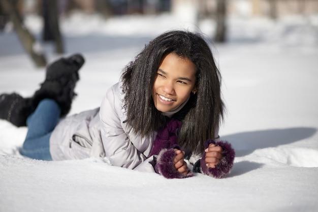 Красивая усмехаясь американская черная женщина лежа в снеге outdoors