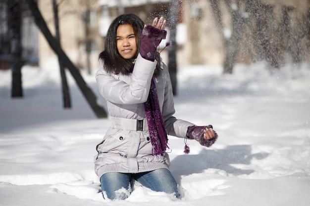 Красивая усмехаясь американская девушка сидя в снеге outdoors играя с снегом