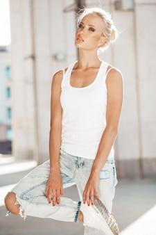 Портрет красивой милой белокурой девушки в белой футболке и джинсах представляя outdoors. милая девушка, стоя на улице фоне