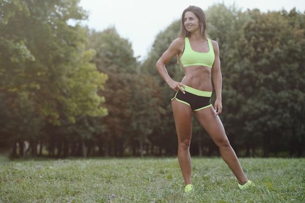 Атлетическая молодая женщина разрабатывая outdoors