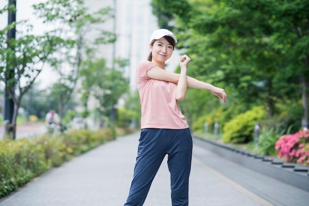 Азиатская молодая женщина работая outdoors