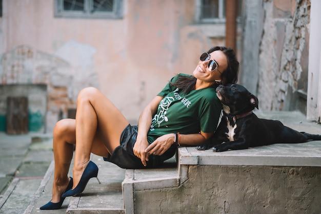 Красивая девушка гуляя ее собака стаффордширский бультерьер outdoors на солнечный день в лете. они сидят на ступеньках во дворе.