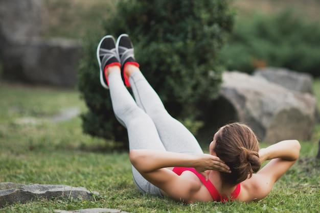 Женщина фитнеса делая тренировку outdoors в парке.