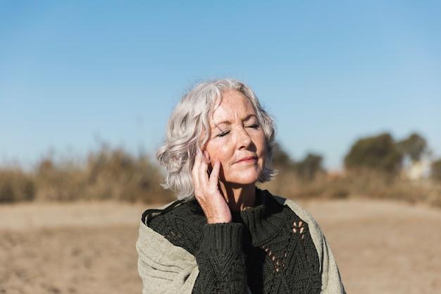 Красивая старшая женщина ослабляя outdoors