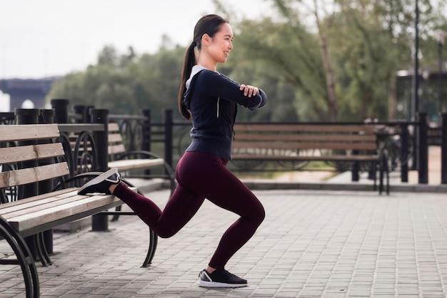 Атлетическая молодая женщина тренируя outdoors
