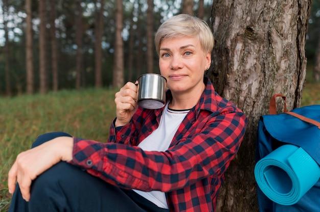 Старшая туристская женщина ослабляя outdoors в природе