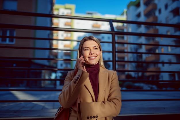 Усмехаясь кавказская очаровательная белокурая молодая женщина в пальто стоя outdoors и говоря на телефоне.