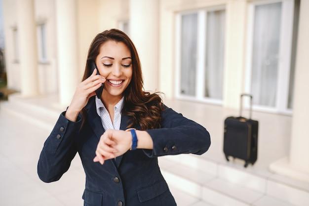 Коммерсантка детенышей усмехаясь кавказская смотря наручные часы и используя умный телефон пока стоящ outdoors. в фоновом режиме багаж. концепция деловой поездки.