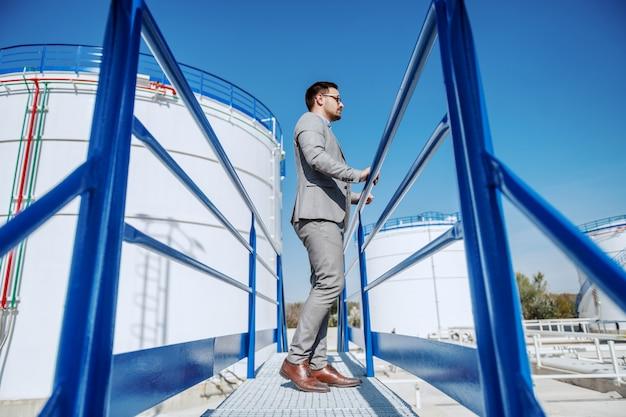 Во всю длину красивого успешного бизнесмена стоя outdoors и смотря его рафинадный завод.