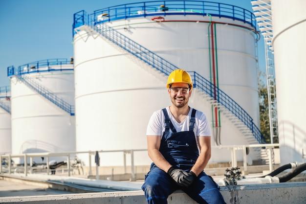 Жизнерадостный кавказский работник в целом и с шлемом на голове сидя outdoors.