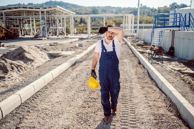 Утомленный кавказский красивый работник в общем гуляя outdoors, держа шлем и вытирая пот.