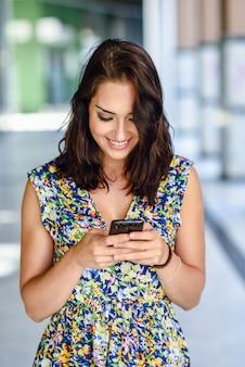 Усмехаясь молодая женщина используя ее умный телефон outdoors.