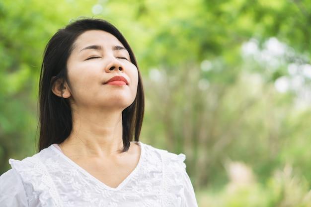 Счастливая азиатская женщина дышая свежим воздухом outdoors