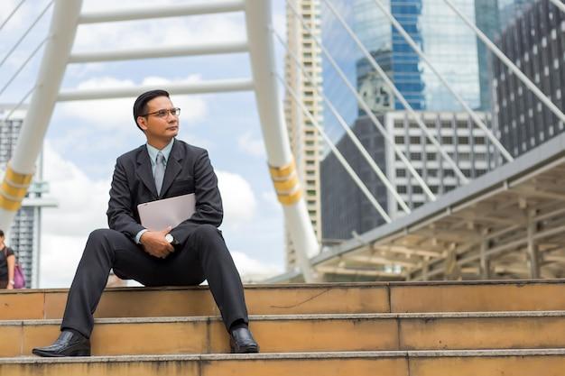 Молодой бизнесмен азии в костюме с его портативным компьютером outdoors, современное здание на предпосылке