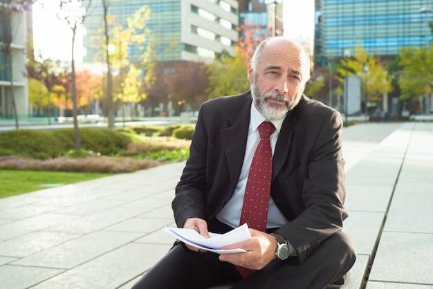 Утомленный бизнесмен сидя с отчетами outdoors