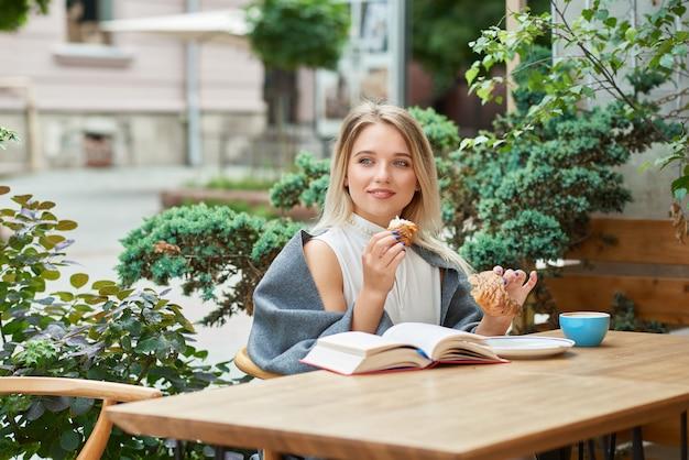 Маленькая девочка с белокурыми волосами есть круассан сидя на салоне кафа outdoors.