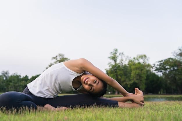 Молодая азиатская йога женщины outdoors держит спокойствие и размышляет пока практикующ йогу