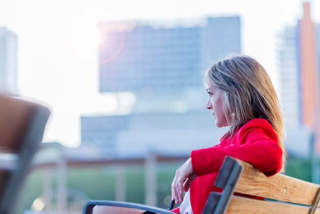 Взгляд низкого угла элегантной белокурой женщины в красной куртке сидя на стенде outdoors пока смотрящ прочь в солнечном дне