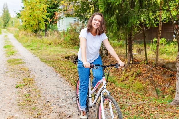 Велосипед катания молодой женщины в парке города лета outdoors. активные люди. хипстер девушка расслабиться и райдер велосипед. велоспорт на работу в летний день. концепция образа жизни велосипедов и экологии.