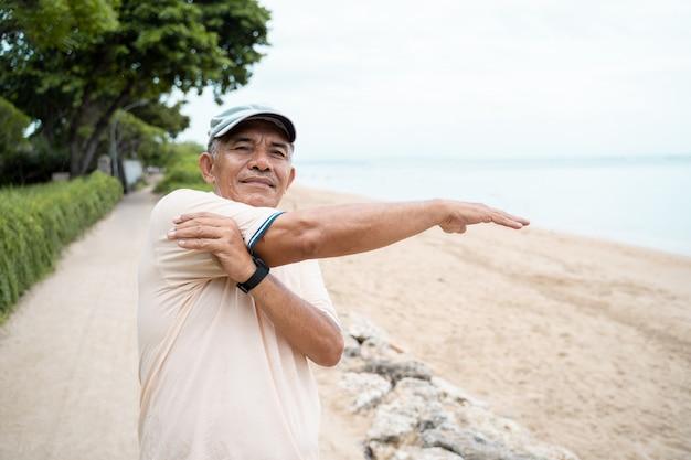 Зрелый азиатский человек делая спорт outdoors