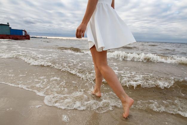 海砂浜の壁にスリムな女性の足。女性の休息とoutdoorson海の海岸を歩きます。旅行や休暇の概念。川の水の近くの短い白いドレスで魅力的で女性の足