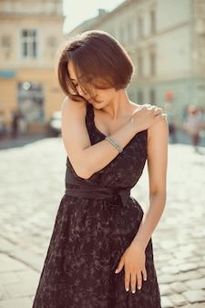 세련된 드레스를 입고 도시 거리에서 포즈를 취한 사랑스러운 갈색 머리 여성의 아웃도트 초상화
