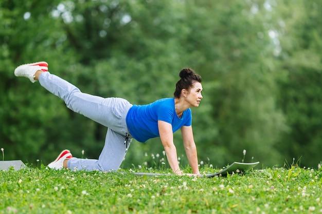 公園でヨガの練習をしている高齢者の女性。年配の女性練習ヨガoutdor