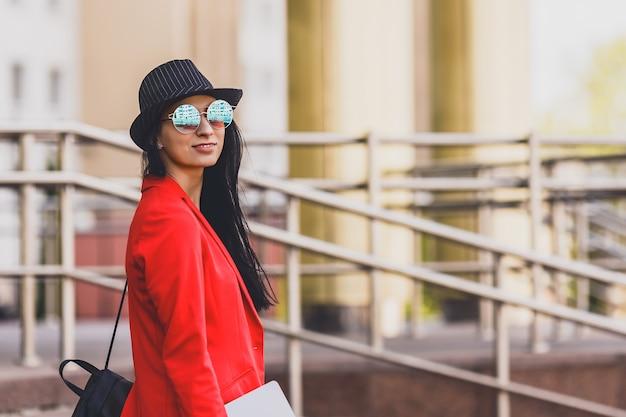 ラップトップoutdorsに取り組んで幸せな流行に敏感な若い女性。大学のキャンパスでラップトップを使用して学生の女の子