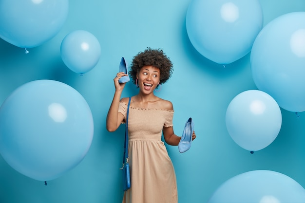 Outfit accessories and footwear. joyful dark skinned woman dances carefree, keeps elegant shoes in hands, has festive mood ready to celebrate special occasion happy to buy clothes on sale in boutique