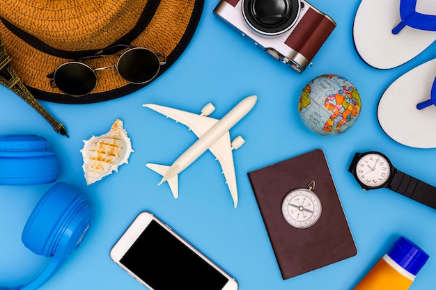Outfit and accessories of traveler on blue background with copy space, travel concept, overhead view of traveler's accessories, essential vacation items,