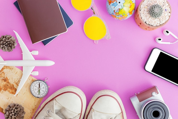 Outfit and accessories of traveler on pink background with copy space, travel concept
