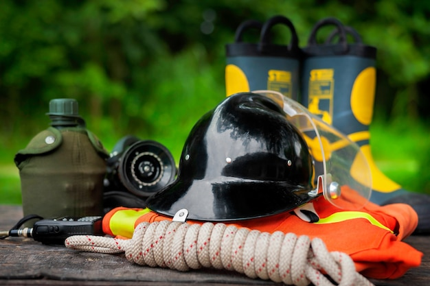 Outfit of firefighter on old table background, fire equipment concept.