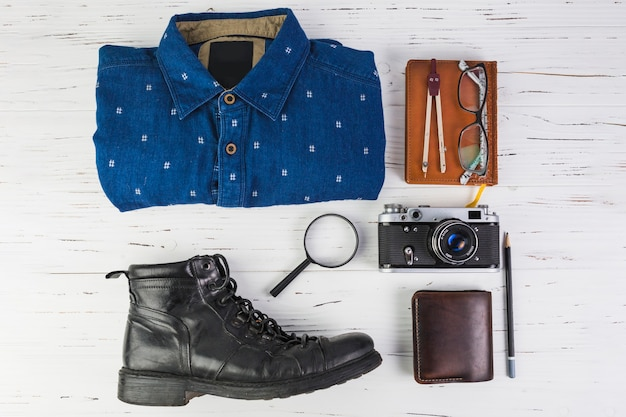 Outfit with travelling accessories on wooden table
