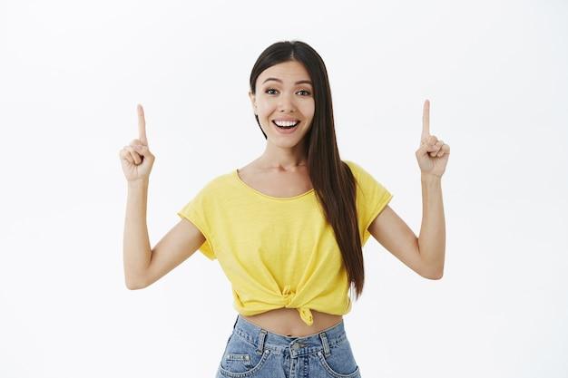 기뻐하는 넓은 미소로 가리키는 검지 손가락을 올리는 노란색 티셔츠에 검은 머리를 가진 나가는 친절하고 즐겁게 매력적인 아시아 소녀