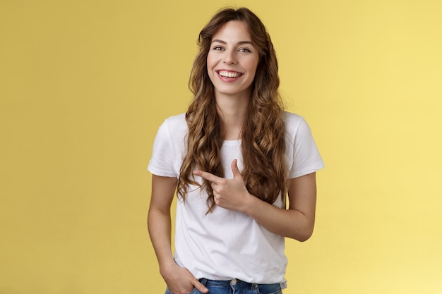 외향적인 매력적인 행복한 예쁜 여성의 곱슬거리는 긴 헤어스타일은 집게손가락을 왼쪽으로 가리키며 광고 웃고 있는 평온한 만족스러운 손 주머니 캐주얼 친근한 포즈 노란색 배경을 나타냅니다.