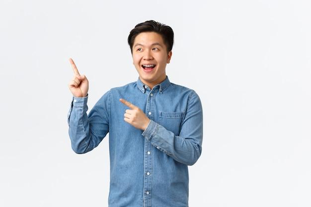 興奮した笑顔で左上隅を見て指さしている発信陽気なアジア人男性