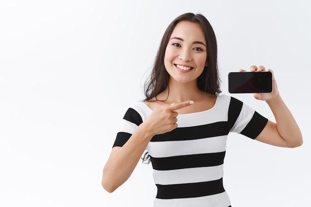 Общительная симпатичная азиатская женщина в полосатой футболке, демонстрирующая смартфон горизонтально возле плеча и указывающая пальцем на дисплей мобильного устройства, представляет новую функцию приложения или предлагает вам веб-сайт