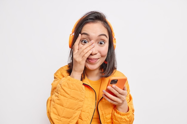 Outgoing pleased teenage girl keeps hand on face feels glad uses smartphone chooses favorite song from playlist wears stereo wireless headphones on ears poses in outerwear against white wall