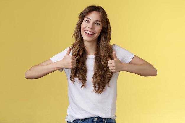 発信ポジティブ自信のある活気のある若い女の子の長い巻き毛のヘアカットは、大きな黄色の背景を笑っているあなたの服のような良い選択を承認するポジティブな返信を親指で示します。ライフスタイル。
