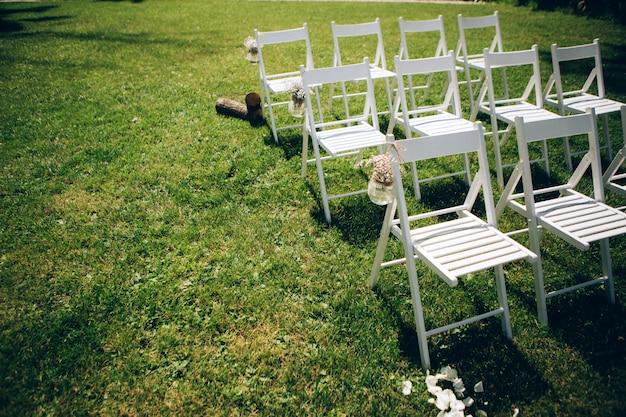 나가는 결혼식. 장식 스튜디오. 녹색 잔디밭에 흰색 나무의 자입니다. 웨딩 축제 아치. 손님을위한 화이트 안락 의자