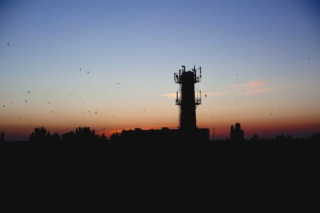 저녁에 비추어 도시의 개요. 타워와 일몰 하늘 위로 새입니다. 산업 도시. 일몰