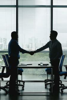 Win-win契約を祝うために握手する2人のビジネスマンの概要