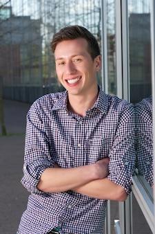 Красивый молодой человек улыбается outoors