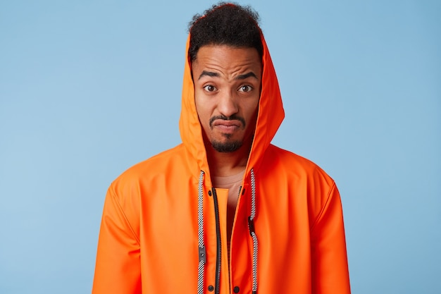 Outraged african american guy in orange rain coat narrows his eyebrows and clenches his lips, looks very displeased, stands.